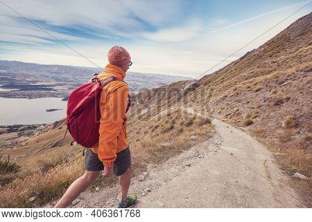 Man walking on hike trail route near Wanaka, beautiful mountains region. Tramping, hiking, travel in New Zealand.