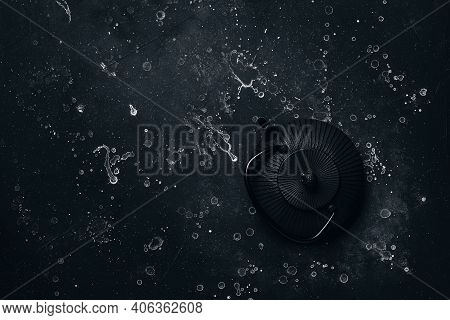 Asian Black Metal Teapot On Black Stone Background. Cast Iron Teapot. View From Above