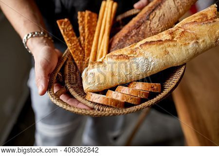 Close Yp Of Man Hand, Holding Basket With Various Bread Freshly Baked.