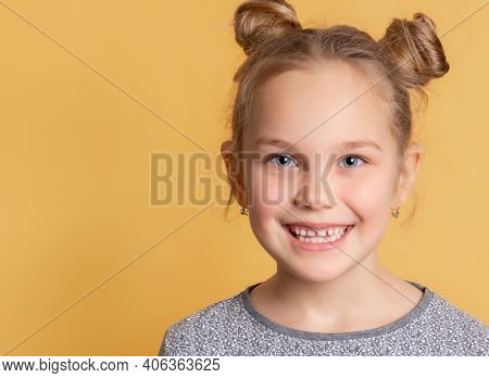 Child Shows His Healthy Teeth. Close Up Of The Face Of A Little Cute Girl Who Is Smiling Showing Tee