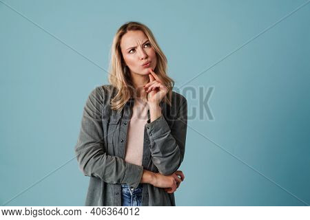 Happy beautiful perplexed girl thinking and looking aside isolated over blue background