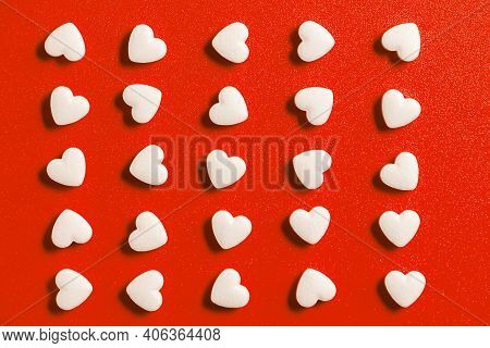 Heart-shaped Tablets, Pattern On Red Background. Medicine, Cardiology, Health Close Up