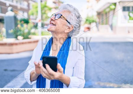 Elder senior woman with grey hair smiling happy outdoors using smartphone