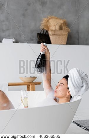 Woman In Lather Holding Bottle And Glass With Champagne In Bathtub