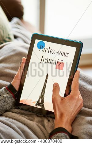a young caucasian man is sitting comfortably in a sofa wrapped in a warming gray blanket, and have his tablet in his hands, with the text do you speak french in its screen