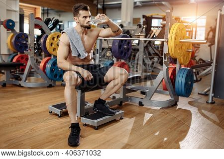 Attractive Athletic Young Man Bodybuilder Fitness Model Drink Water After Exercise With Barbell On T