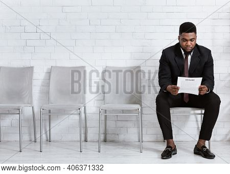 Millennial Black Man Reading His Resume While Waiting For Job Interview At Office Hall, Empty Space.