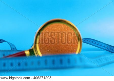 Magnifying Glass And Orange On A Blue Background As A Symbol Of Cellulite. Concept Anti-cellulite Pr