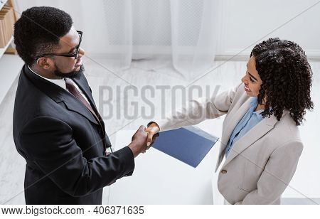 Human Resources Manager Shaking Hands With Successful Vacancy Applicant At Office, Above View. Headh