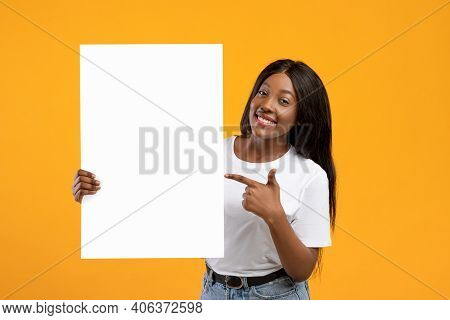Cheerful African American Young Lady Pointing At Empty Advertising Placard In Her Hand, Yellow Studi