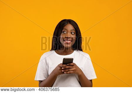 Smiling African American Young Woman Using Mobile Phone And Looking Aside, Copy Space, Yellow Studio