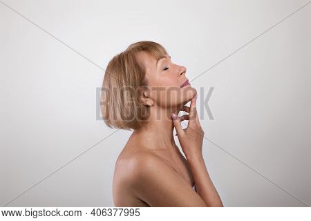 Side View Of Feminine Nude Senior Woman Touching Silky Skin On Her Neck, Light Studio Background. Ch
