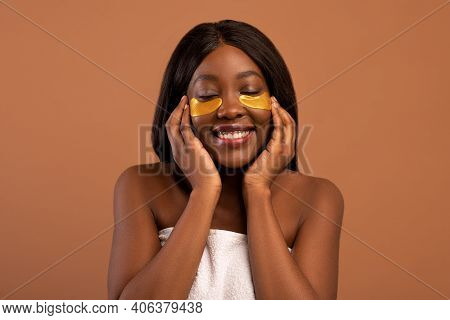 Closeup Of Pretty Joyful Young Black Lady With Closed Eyes Applying Golden Hydrogel Eye Patches Over