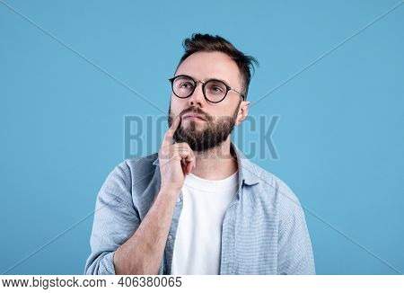 Portrait Of Pensive Bearded Man In Glasses Touching His Chin, Deep In Thought Over Blue Studio Backg