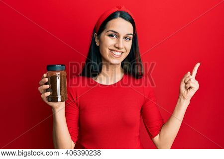 Young hispanic woman holding soluble coffee smiling happy pointing with hand and finger to the side