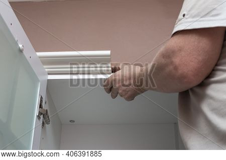 Furniture Assembly. A Man Assembles A Kitchen Set, Attaches Stucco Molding To The Upper Cabinets.