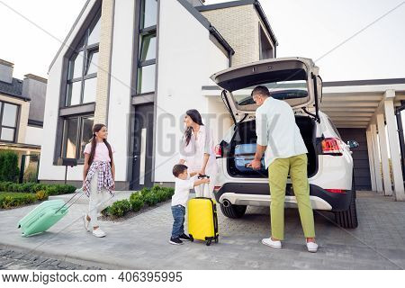 Proto Portrait On Full Family With Small Kids Put Baggage Suitcases In The Car Smiling Together Befo