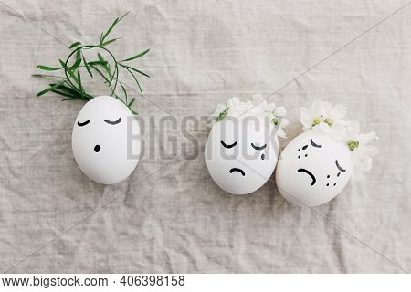 Easter Concept. Natural Eggs With Sad Crying And Calm Faces In Cute Floral Wreaths On Linen Fabric,