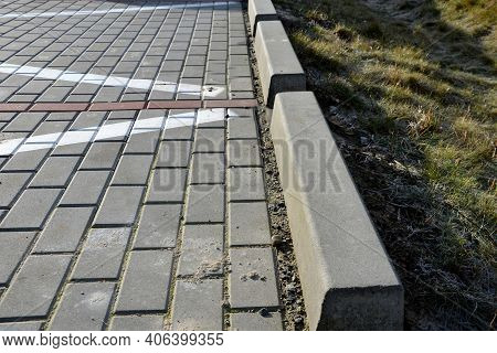 Installation Of Concrete Curbs With Gaps That Let Water Into The Park Into The Ditch, Where It Seeps