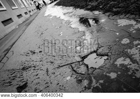 A Picture Of The Pothole On The Pavement. The Water Is Inside, The Spatter From The People Or Bikes