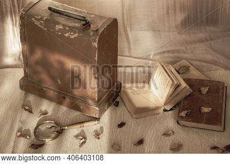 Old Books Next To A Wooden Chest, Magnifier. Light And Shadow, Autumn Day. Vintage Style. Concept Of
