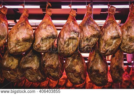 Detail Of A Group Of Spanish Ham 'jamon Serrano' Hanging At A Stand In The Market 'mercat Central' I