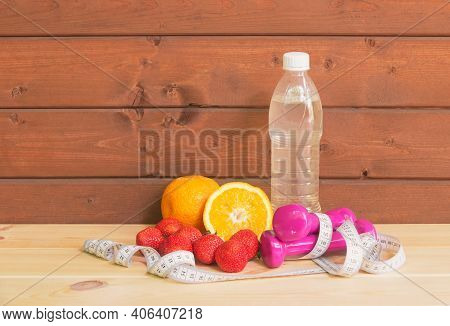 Dumbbells, Bottle Of Water, Fresh Oranges, Strawberry And Measure Tape. Fitness And Healthy Eating C