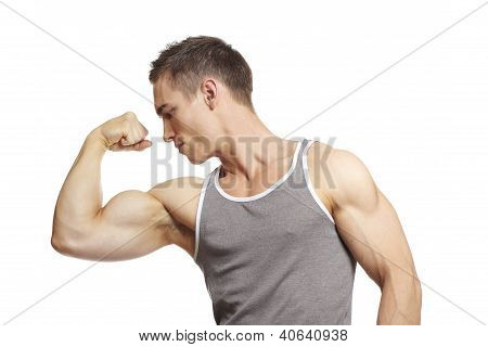 Muscular Young Man Flexing Arm Muscles In Sports Outfit