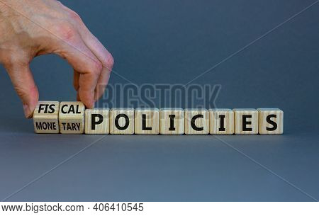 Fiscal Or Monetary Policies Symbol. Businessman Turns Wooden Cubes, Changes Words Fiscal Policies To