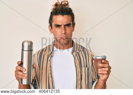 Young hispanic man drinking mate infusion skeptic and nervous, frowning upset because of problem. negative person.