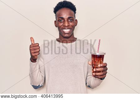 Young african american man drinking mate infusion smiling happy and positive, thumb up doing excellent and approval sign