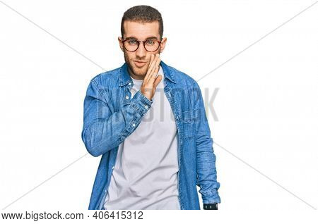 Young caucasian man wearing casual clothes hand on mouth telling secret rumor, whispering malicious talk conversation