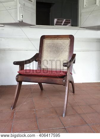 Classic Antique Wooden Chair With Mesh Backrest And Red Cushion. Front View Of Colonial Solid Wood A