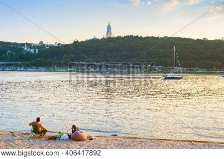 Kiev, Ukraine - August 05, 2020: Couple Fishing On The Beach Of Dnipro River. Kiev Pechersk Lavra In