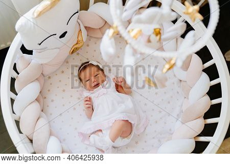 Top View. Newborn Girl In Beautiful Round Cradle With Mobile Made Of Plush Toys