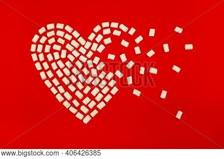 White Marshmallow Laid Out Of Heart Shape On Red Background.