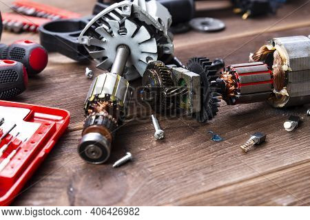 Power Tool Repair. Details Of Electrical Appliance And Repair Tools On A Wooden Table In A Repair Sh