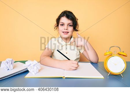 Cute hispanic child studying for school writing book sitting on the table pointing finger to one self smiling happy and proud