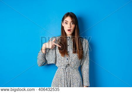 Surprised Young Woman Pointing At Herself With Disbelief, Being Chosen Or Picked, Standing In Dress