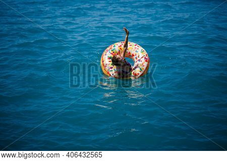 Young Woman Floating On An Inflatable Big Donut In The Transparent Turquoise Sea. View Of A Slender
