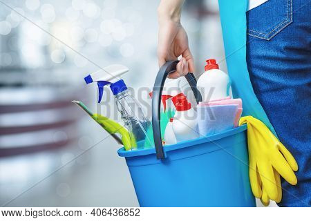 Cleaning Lady Holding A Bucket Of Cleaning Products In Her Hands On A Blurred Background.