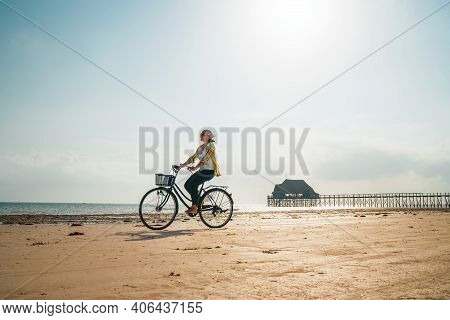 Young Woman Dressed Light Summer Clothes Riding Old Vintage Bicycle With Front Basket On The Lonely