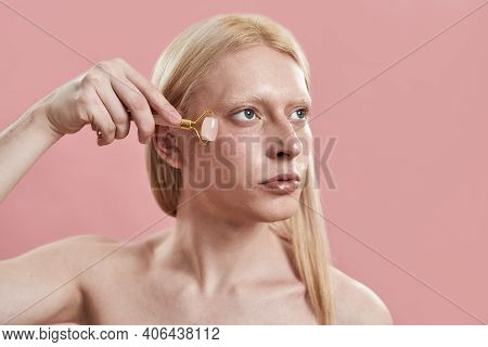 Young Caucasian Man With Long Blond Hair Using Quartz Roller For Under Eye Massage While Standing On