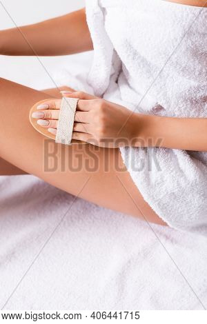 Partial View Of Woman Wrapped In Towel Exfoliating Skin On Leg.