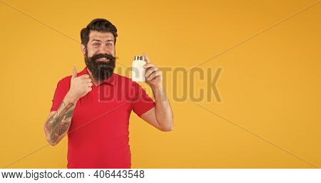 Anabolic And Steroids. Brutal Bearded Hipster Man Hold Vitamin. Medicine Pills And Drugs. Haircare.