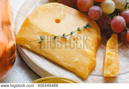 Cheddar Cheese With Grapes, Pink Wine, Honey. Wine Cheese Snacks For A Romantic Dinner. Aged Dutch G