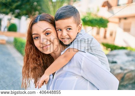 Adorable latin mother and son smiling happy hugging at the city.
