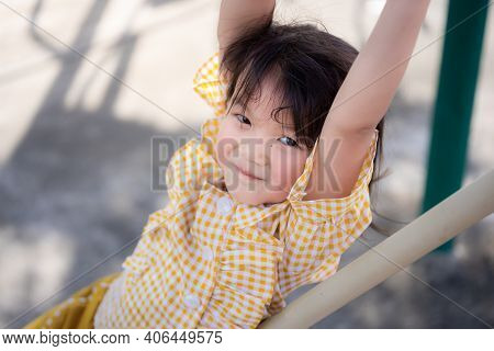 Active Child Play Trapeze In The Playground. Beautiful Kid With A Sweet Smile Looking At The Camera.