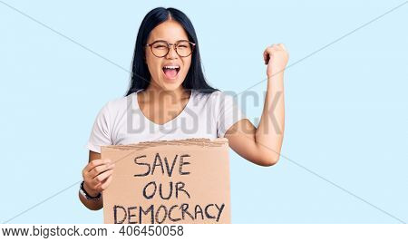 Young beautiful asian girl holding save our democracy protest banner screaming proud, celebrating victory and success very excited with raised arms