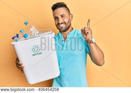 Handsome man with beard holding recycling wastebasket with plastic bottles surprised with an idea or question pointing finger with happy face, number one